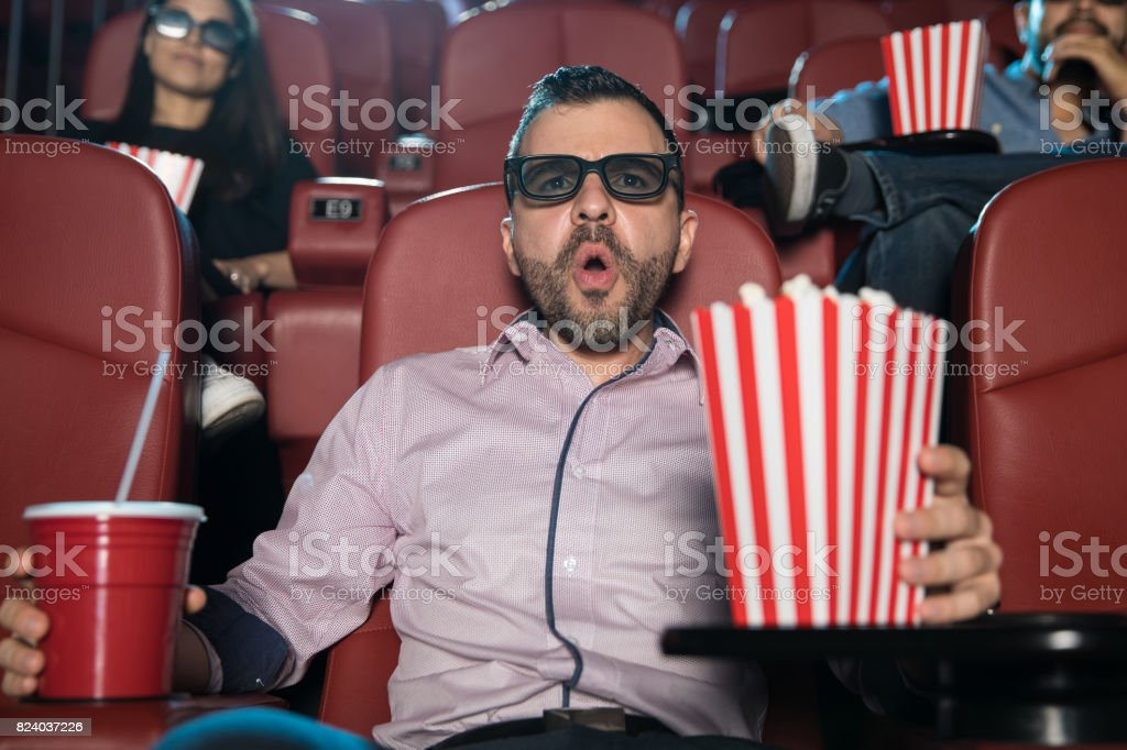 Man looking surprised at the movies stock photo