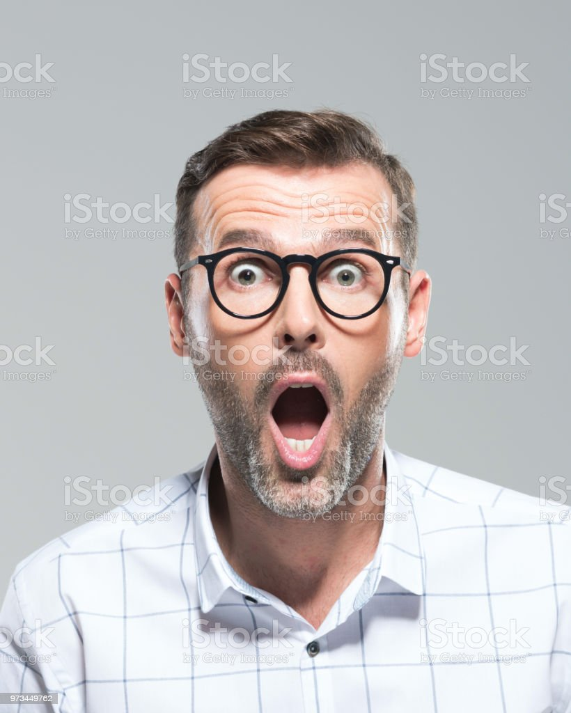 Man looking surprised Headshot of mature man looking at camera with mouth open. Man looking surprised on grey background. 30-39 Years Stock Photo