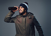 An Indian bearded male dressed in a warm jacket and a hat looking through beer bottle.