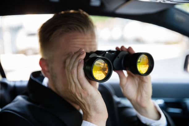 man looking through binocular - stalking stock photos and pictures