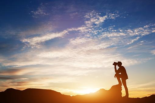 Man looking through binoculars at sunset.