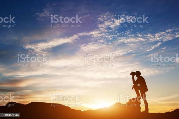 Photo of Man looking through binoculars at sunset.