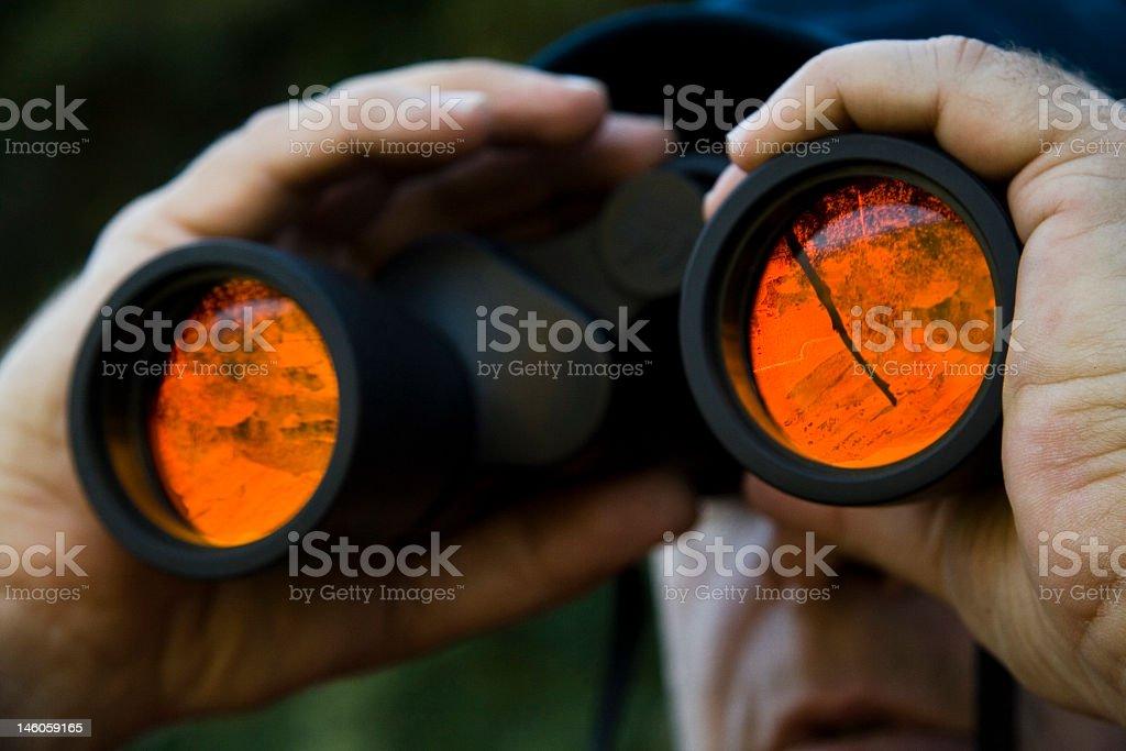 A man looking through binoculars stock photo