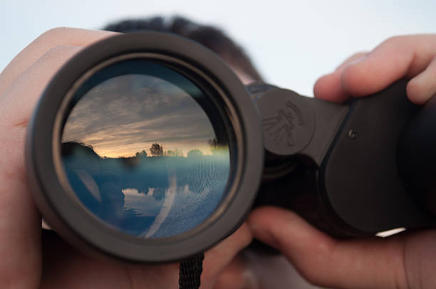 man looking through binoculars stock photo