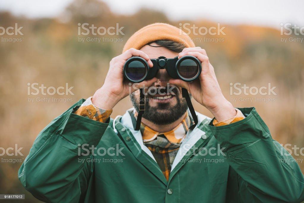 man looking through binoculars Handsome man in hat and raincoat looking through binoculars Adults Only Stock Photo