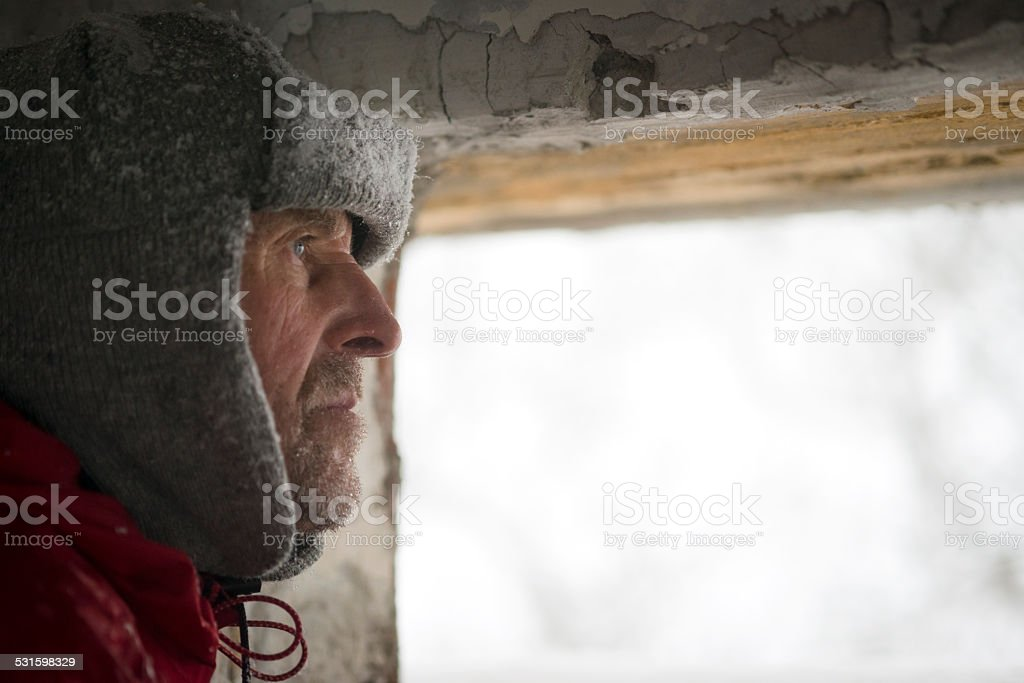 Man Looking  through Great War's Bunker Porthole , Snowing, Alps, Europe stock photo