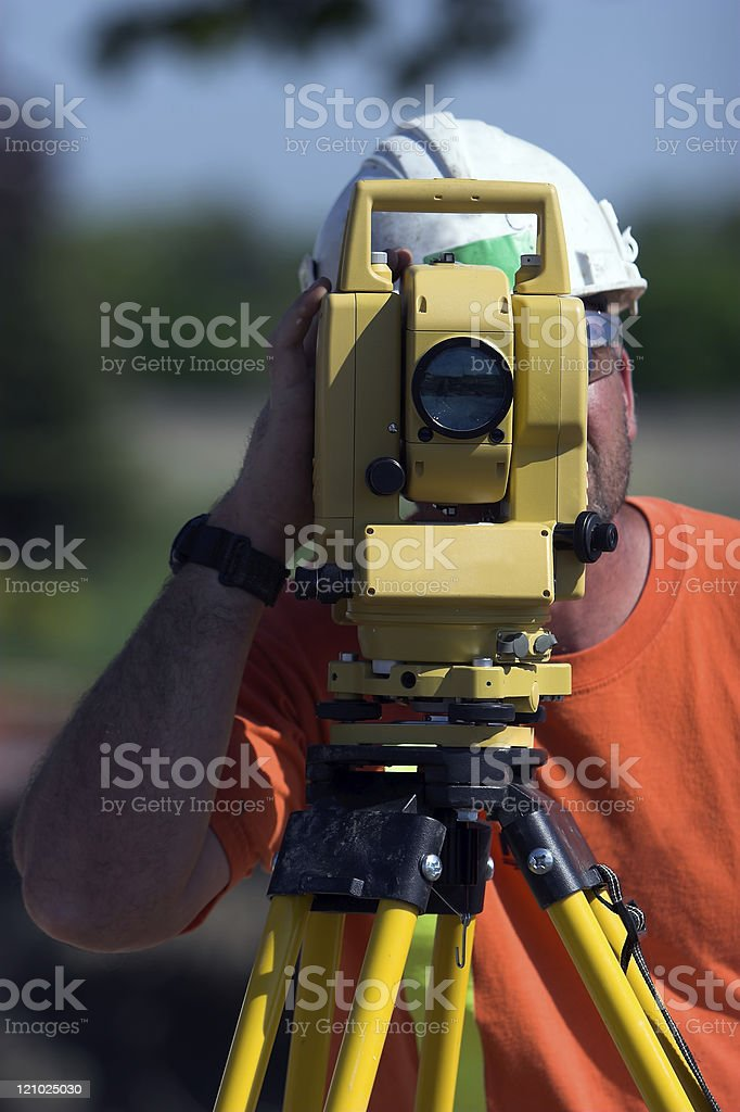 Man looking through surveying equipment royalty-free stock photo