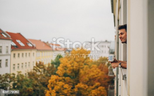 istock Man looking through the apartment window in Berlin Prenzlauer Berg 638179080