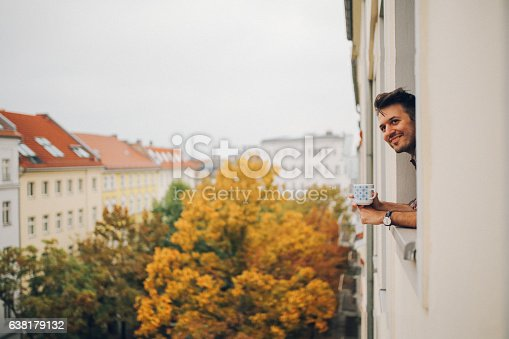 istock Man looking through the apartment window in Berlin Prenzlauer Berg 638179132