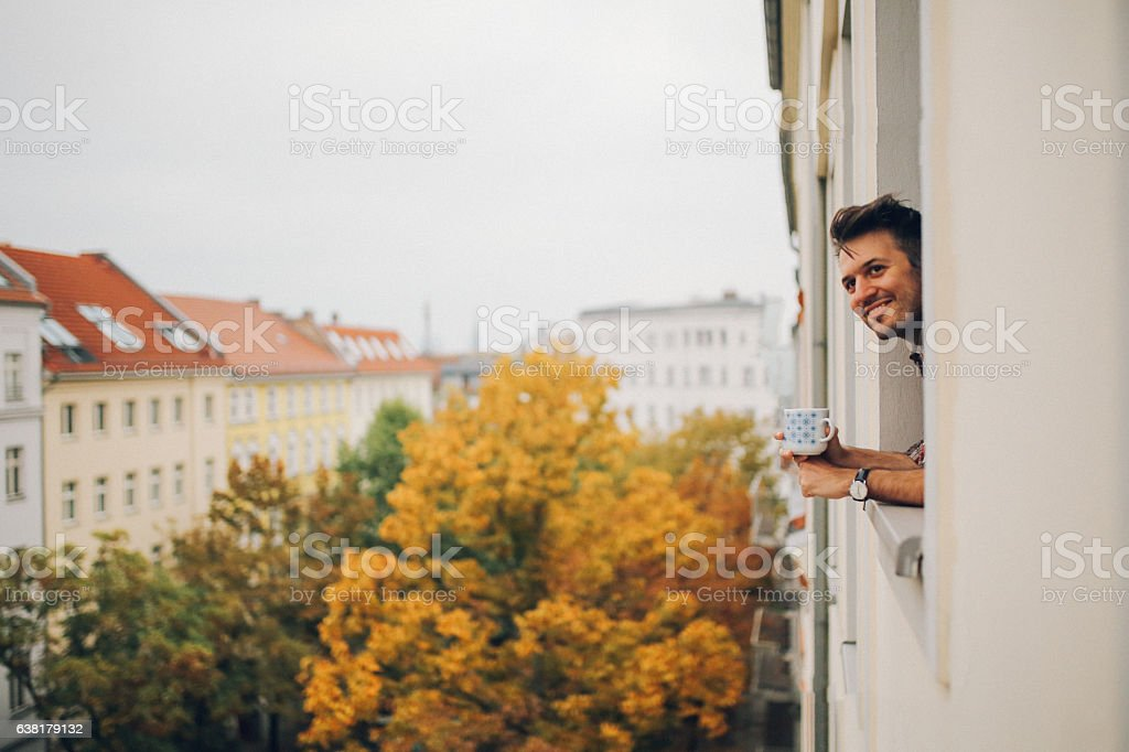 Man looking through the apartment window in Berlin Prenzlauer Berg stock photo