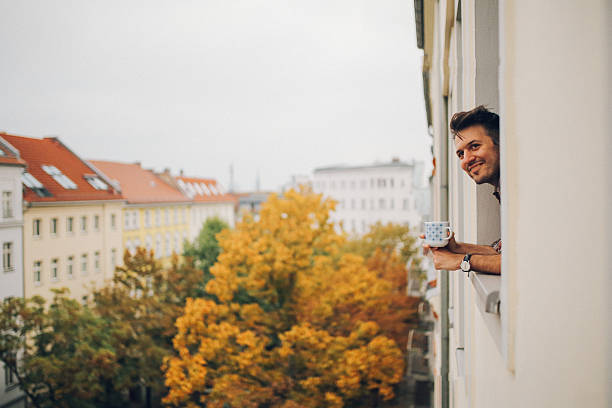 man looking through the apartment window in berlin prenzlauer berg - berlin street bildbanksfoton och bilder