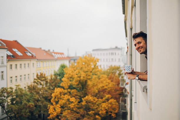 man looking through the apartment window in berlin prenzlauer berg - kreuzberg stock-fotos und bilder