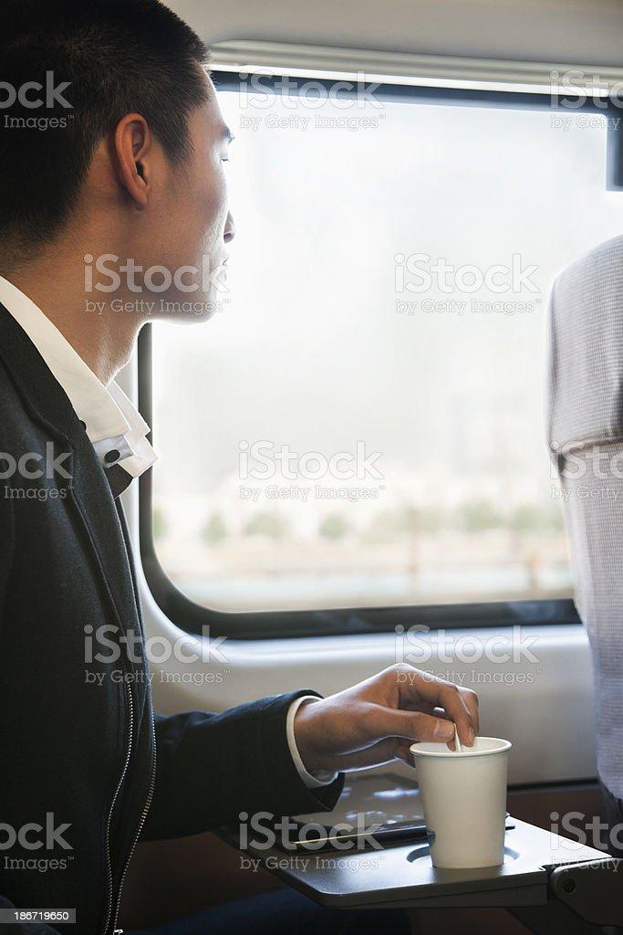 Man Looking Through Train Window While Stirring His Coffee royalty-free stock photo