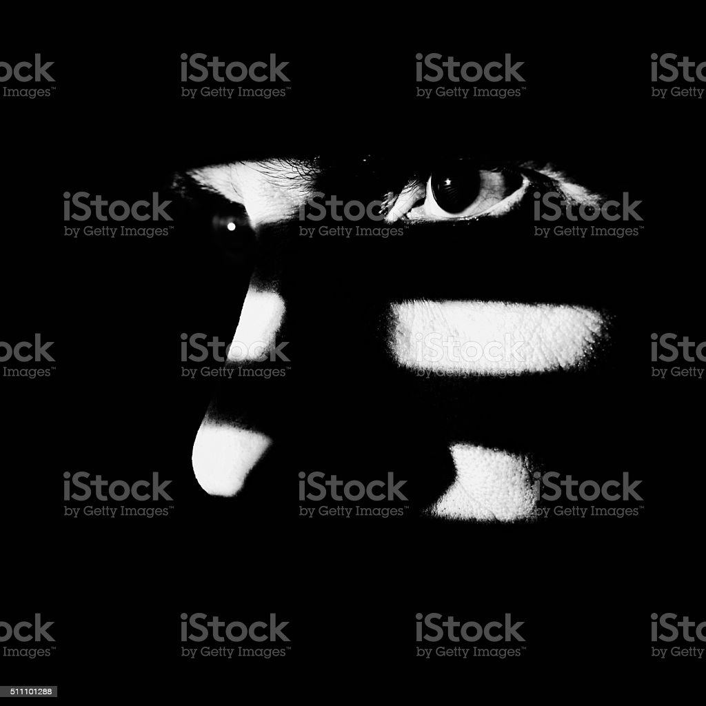 Man looking through window blind high contrast black white stock photo