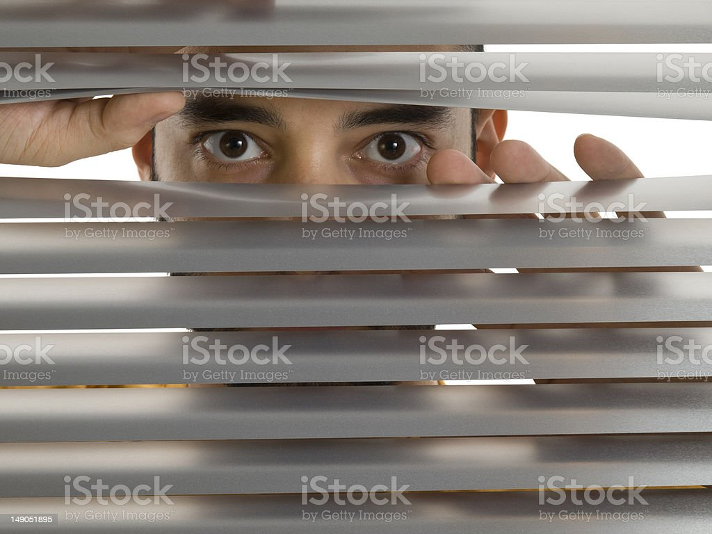 Man looking through window blinds royalty-free stock photo