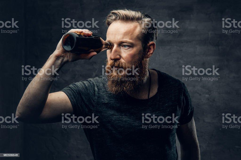 Um homem olhando através de garrafas de cerveja. - Foto de stock de Alcoolismo royalty-free