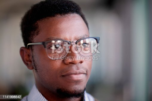 611876426 istock photo Man looking to the side out of window in office 1141998542