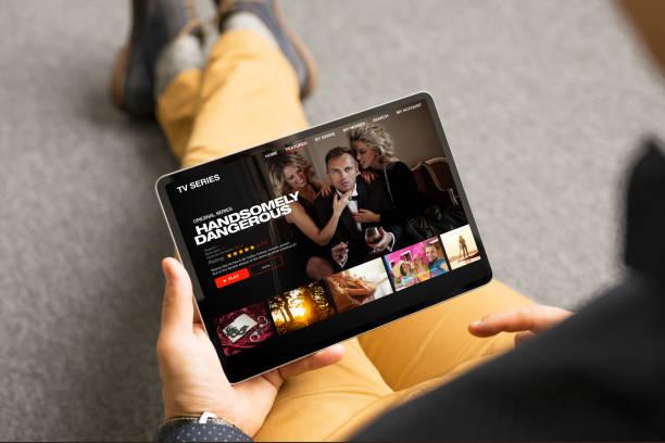pria mencari serial tv dan film di tablet digitalnya - menonton potret stok, foto, & gambar bebas royalti