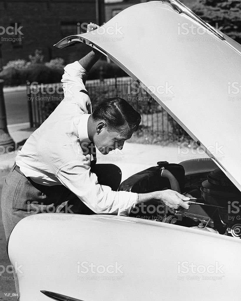 Man looking under hood of car royalty-free stock photo