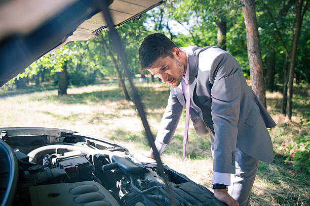 Man looking under the hood of car Man in suit looking under the hood of breakdown car vehicle hood stock pictures, royalty-free photos & images