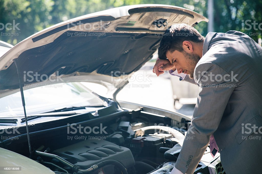 Man looking under the hood of car stock photo
