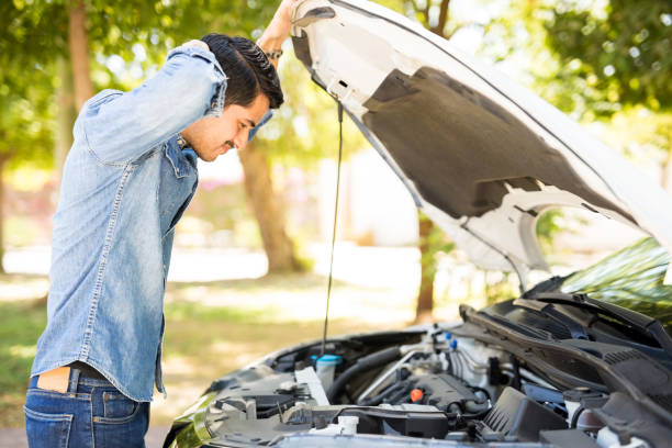 man looking under the hood on broken car - stranded stock pictures, royalty-free photos & images