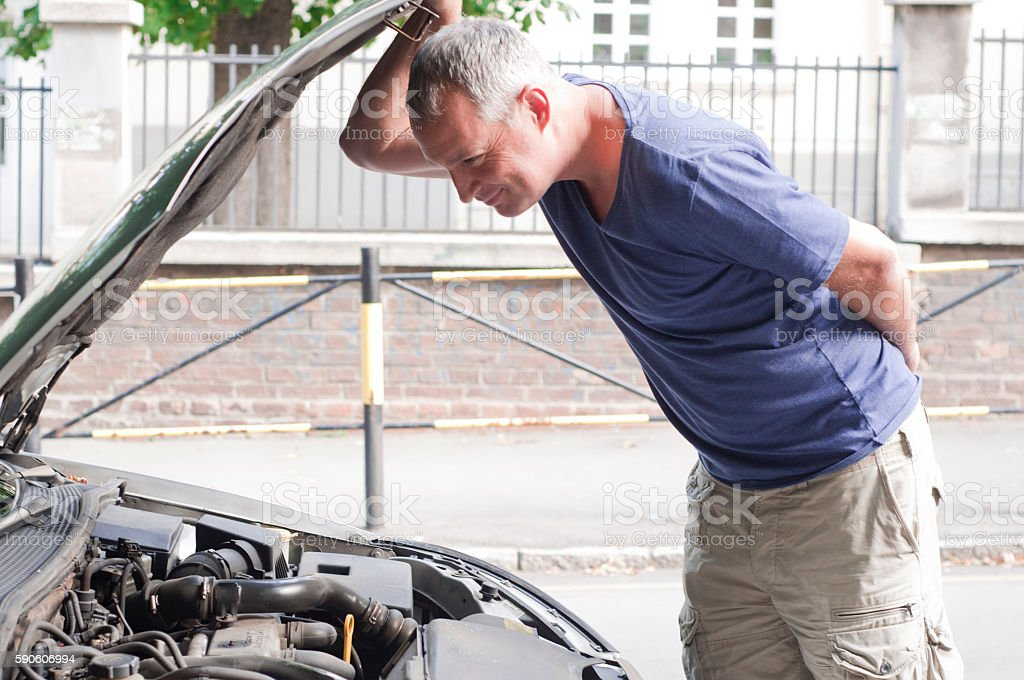 Man looking under the hood. stock photo