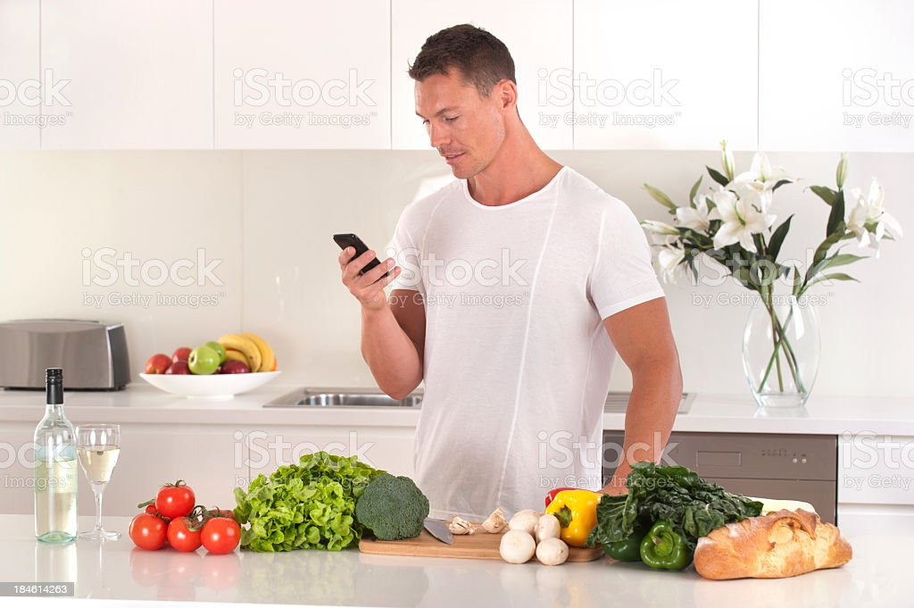 Man looking up a recipe on his mobile phone royalty-free stock photo