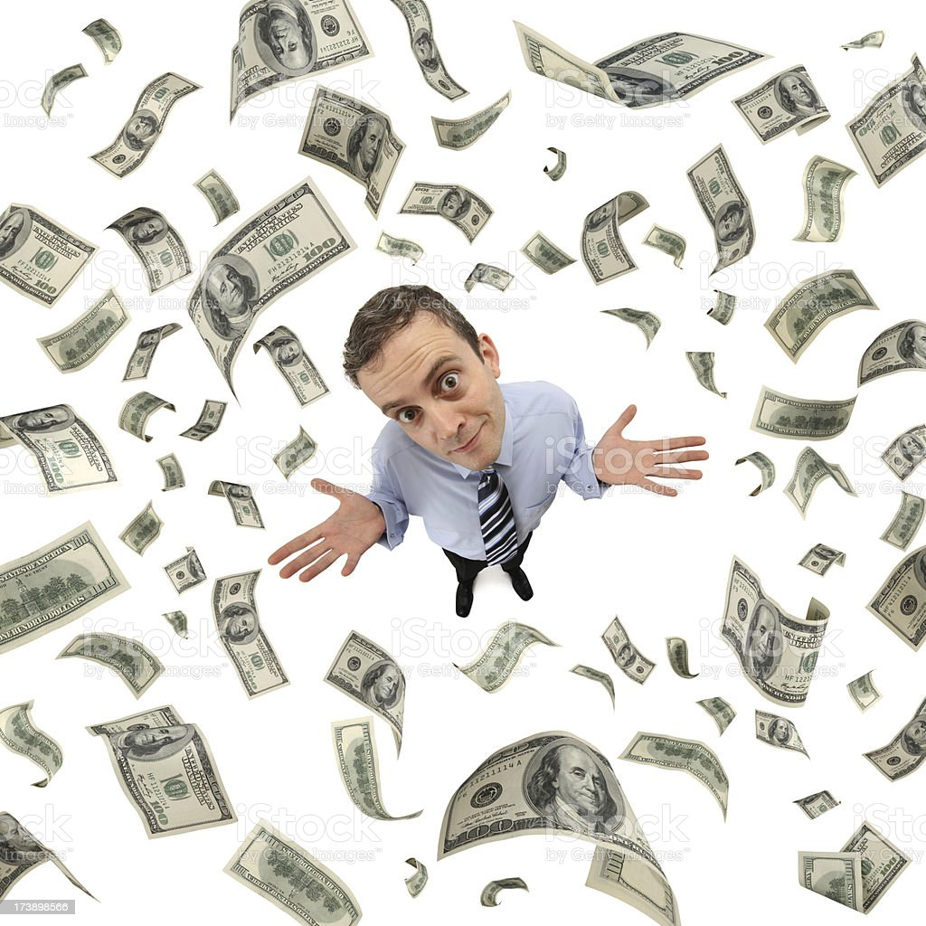 A man looking up as hundred dollar bills fall from the sky stock photo