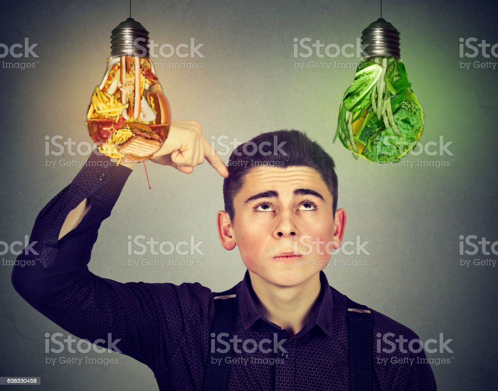 man looking up at junk food vegetables light bulb stock photo