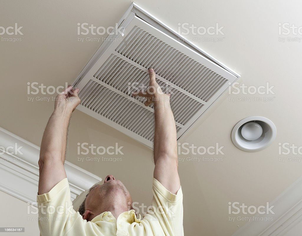 Man looking up opening air conditioning filter in ceiling stock photo
