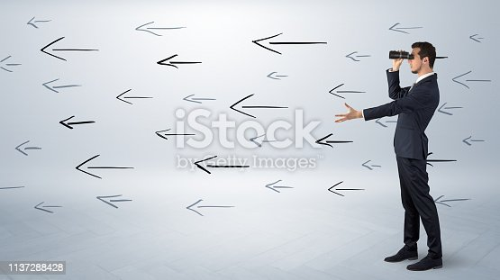 904389218istockphoto Man looking with binoculars and arrows around 1137288428