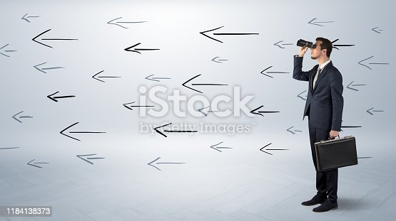 904389218istockphoto Man looking with binoculars and arrows around 1184138373