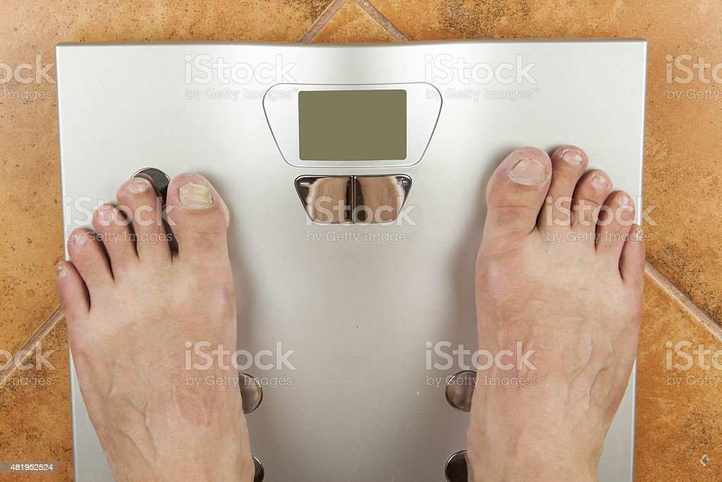 Man looks at a personal scale. stock photo