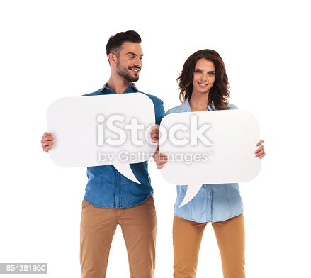 854381780istockphoto man looks at his girlfriend while both hold speech bubbles 854381950