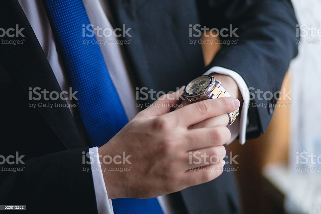 man looks at his watch stock photo