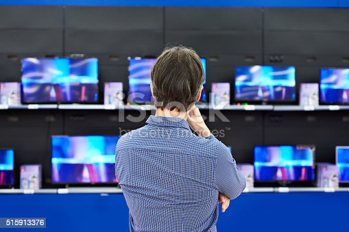 Man looks at LCD TVs in supermarket