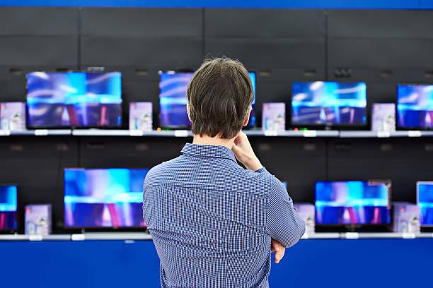 mann sieht in lcd-fernseher im speichern - freizeitelektronik stock-fotos und bilder