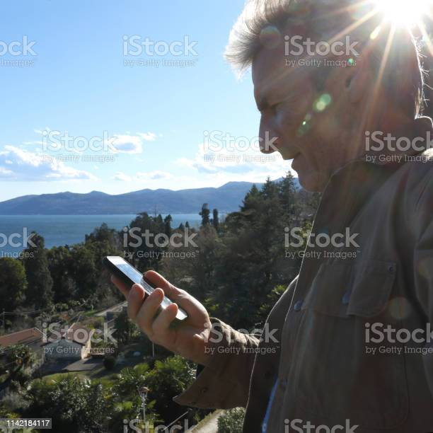Photo of Man looks at phone while he stands on hillside