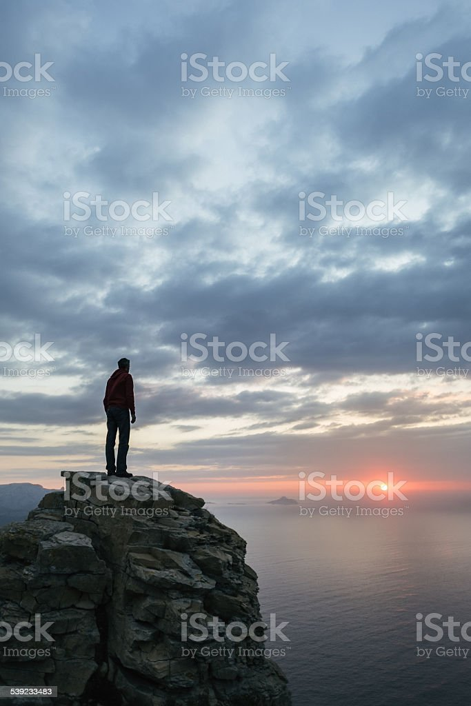 Man looks at the seascape from a cliff royalty-free stock photo