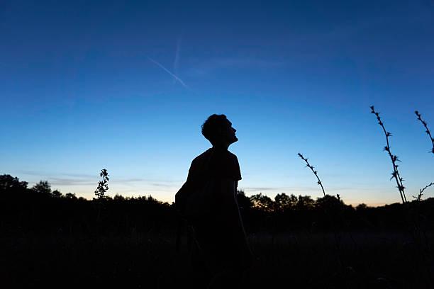 man looks at the sky hopefully - walking home sunset street bildbanksfoton och bilder