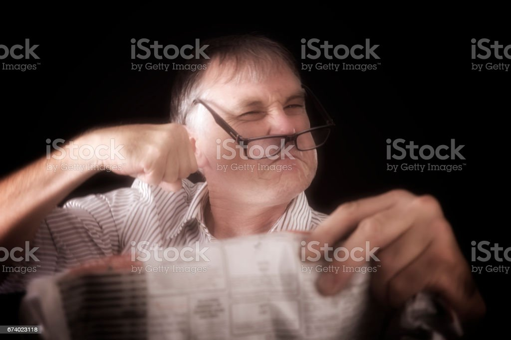 Man looks content while reading the newspaper royalty-free stock photo