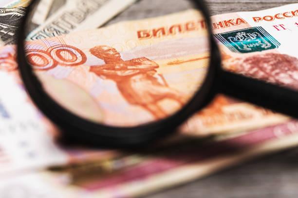 한 남자가 러시아 돈으로 돋보기를 보고 진위를 확인합니다. - 러시아 루블 뉴스 사진 이미지