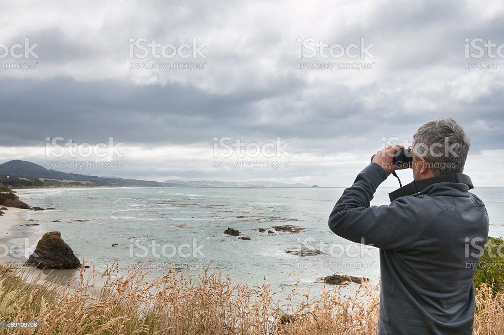 Man looks in binocular across ocean bay stock photo