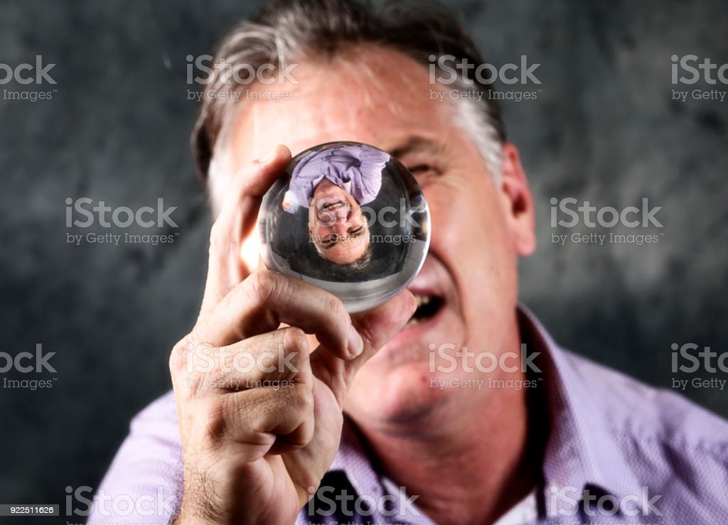 Man looks into crystal ball stock photo