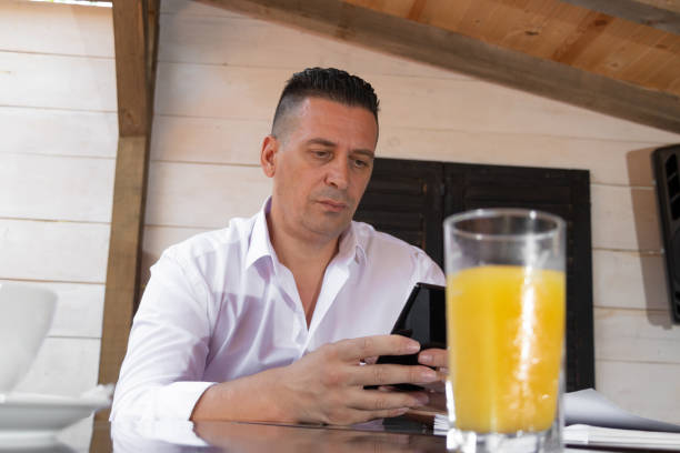 A man looks into the phone in the cafe stock photo