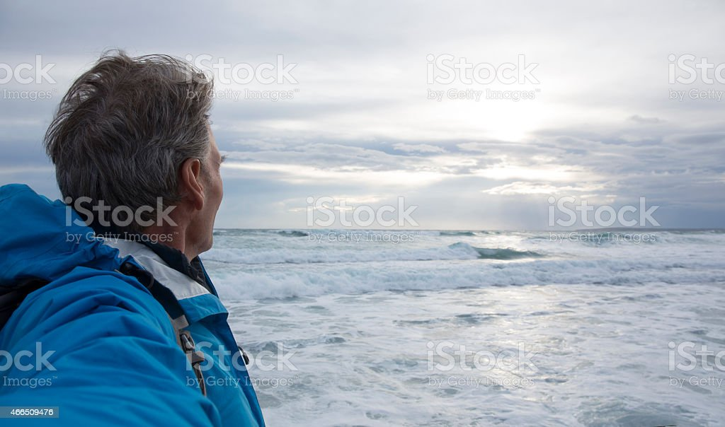Man looks out across sea after storm stock photo
