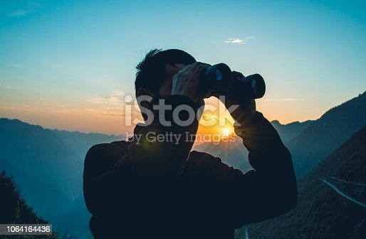 Man looks through binoculars in mountain