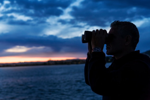 Man looks through binoculars
