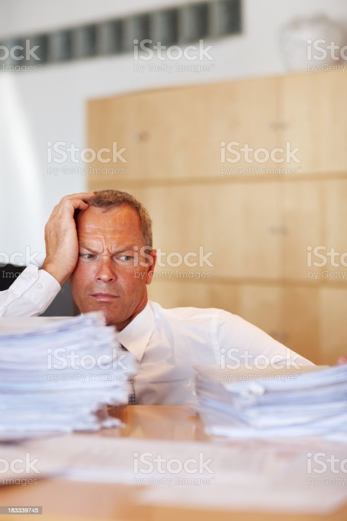Man looks to be defeated by piles of paperwork royalty-free stock photo